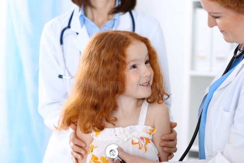 Medico che esamina una bambina con lo stetoscopio Concetto di sanità e della medicina immagine stock libera da diritti