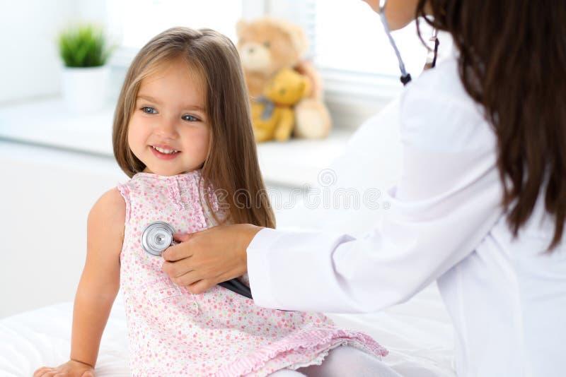 Medico che esamina una bambina secondo lo stetoscopio fotografia stock libera da diritti