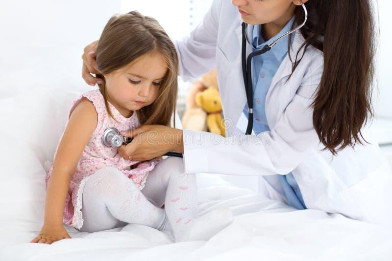 Medico che esamina una bambina secondo lo stetoscopio immagini stock libere da diritti