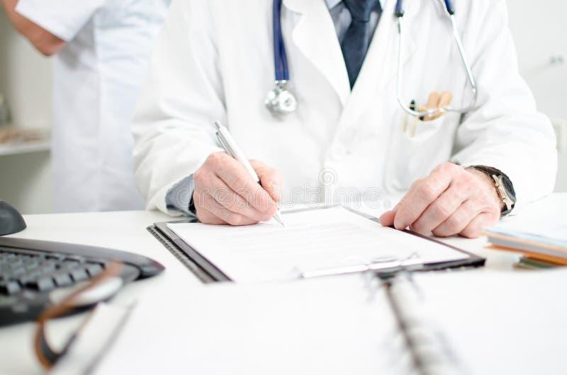 Medico che firma una perizia medica fotografia stock libera da diritti
