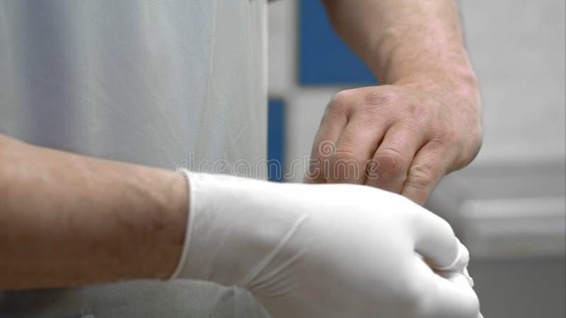 Medico che indossa il guanto chirurgico sterilizzato bianco fotografia stock libera da diritti