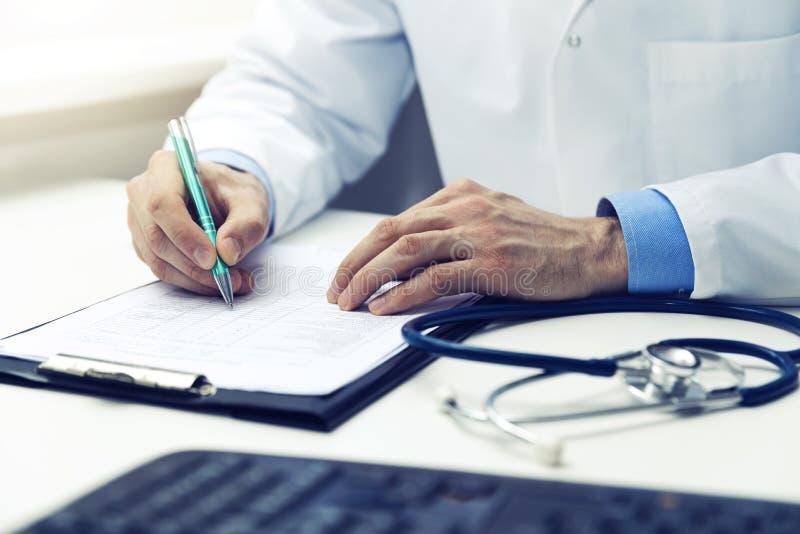 Medico che lavora nei documenti di scrittura dell'ufficio immagine stock libera da diritti