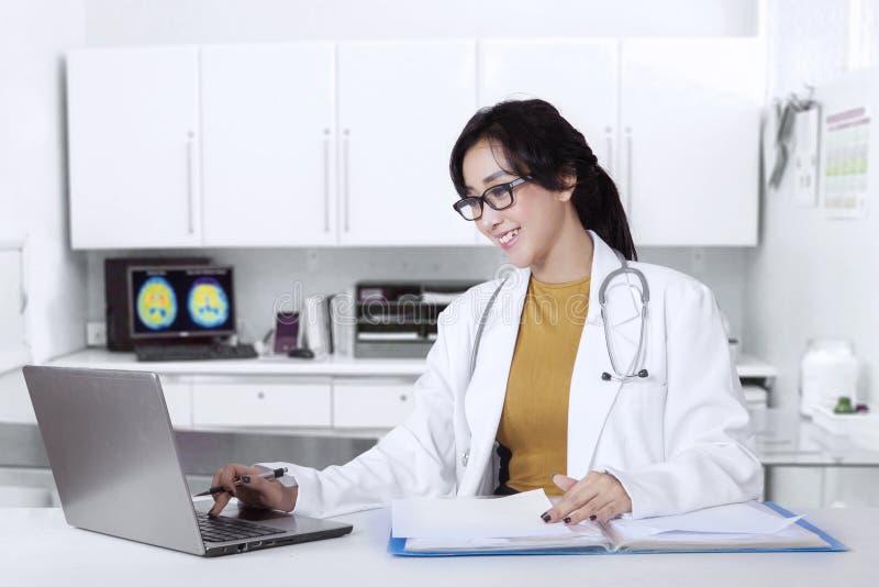 Medico che lavora nella clinica con il computer portatile immagini stock libere da diritti