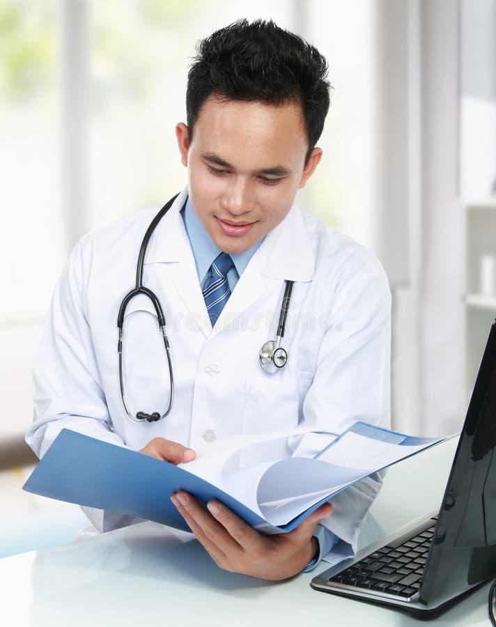 Medico che legge un documento dell'archivio fotografia stock libera da diritti