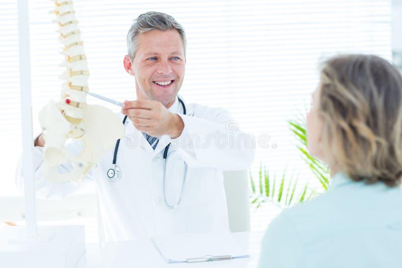 Medico che mostra al suo paziente un modello della spina dorsale immagini stock