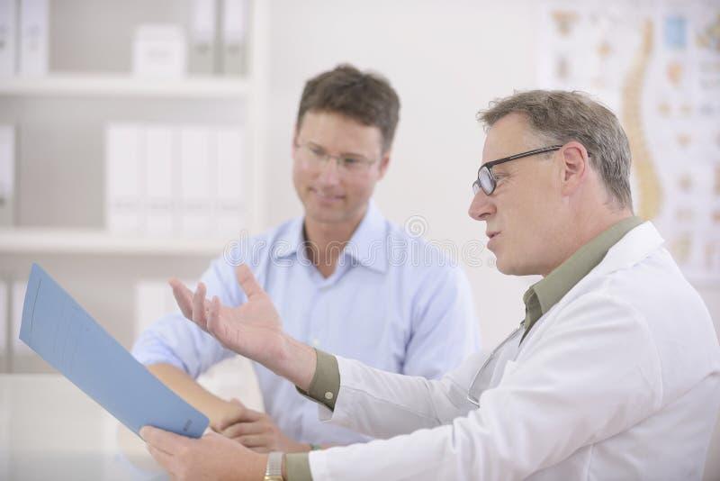 Medico che mostra i risultati al paziente fotografia stock