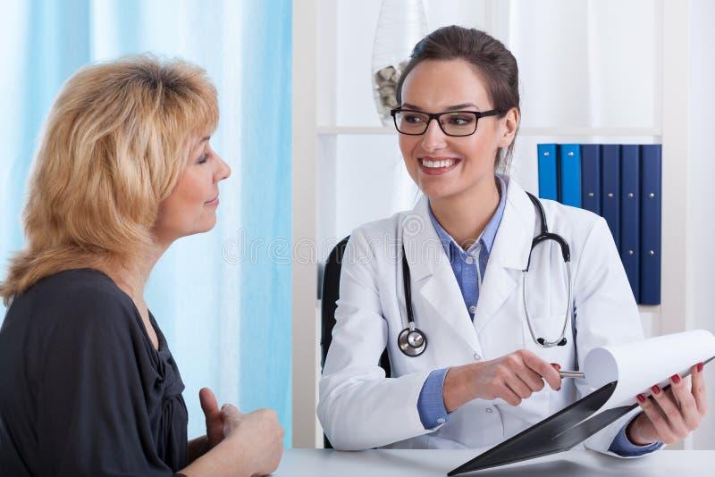 Medico che mostra i risultati dei test del paziente fotografia stock libera da diritti