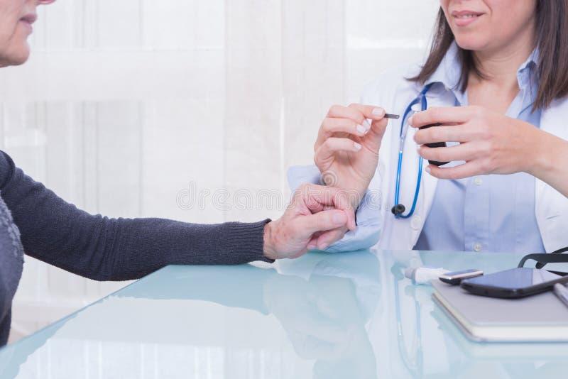 Medico che mostra le strisce test pazienti del diabete fotografia stock