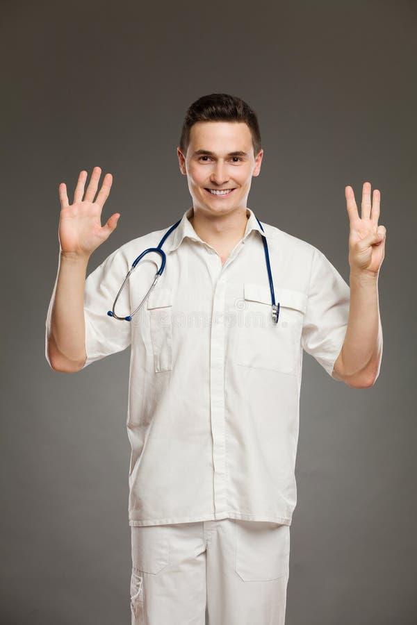 Medico che mostra numero otto immagine stock