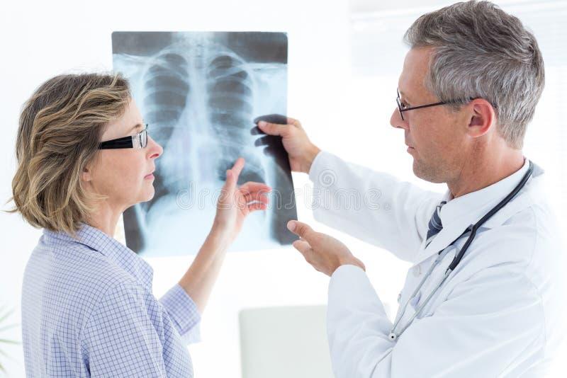 Medico che mostra raggi x al suo paziente fotografie stock libere da diritti