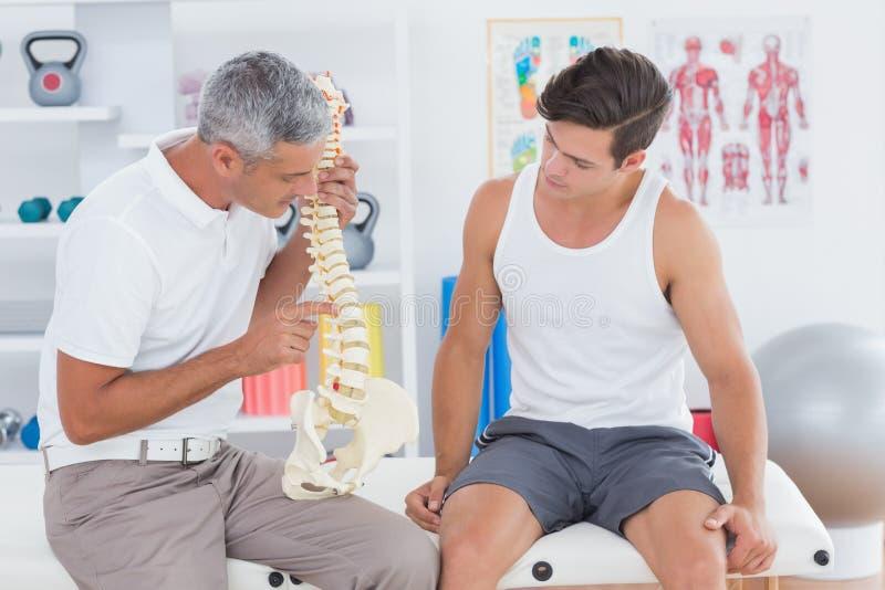 Medico che mostra spina dorsale anatomica al suo paziente fotografia stock libera da diritti