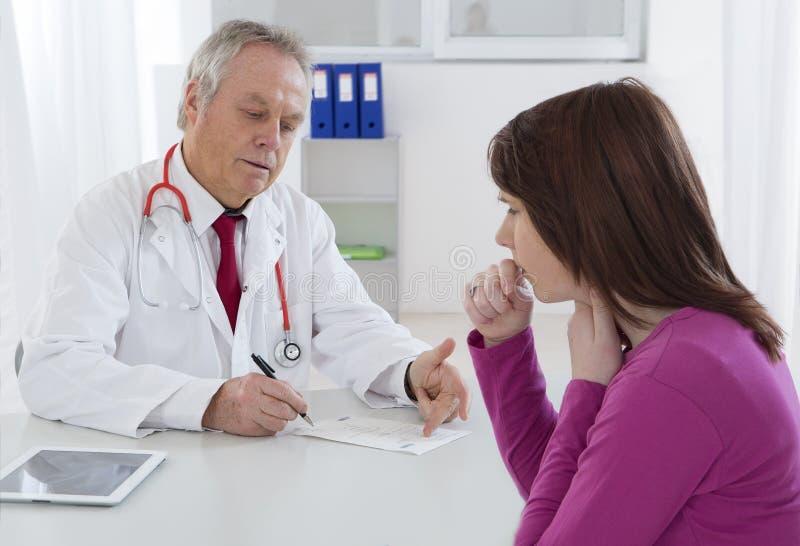 Medico che parla con suo giovane paziente femminile fotografia stock