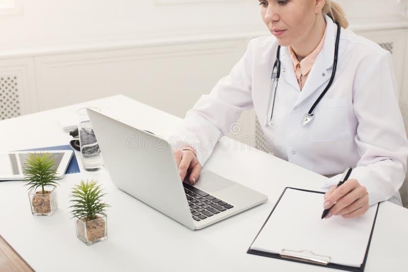 Medico che per mezzo del computer portatile e scrivendo le note all'ufficio fotografia stock libera da diritti