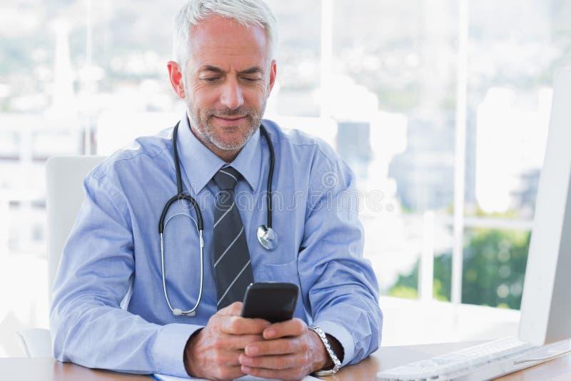 Medico che per mezzo del suo smartphone fotografia stock libera da diritti