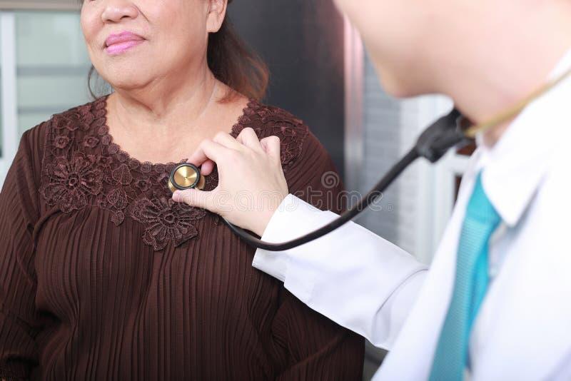 Medico che per mezzo dello stetoscopio al cuore del paziente della donna dell'esame fotografie stock libere da diritti