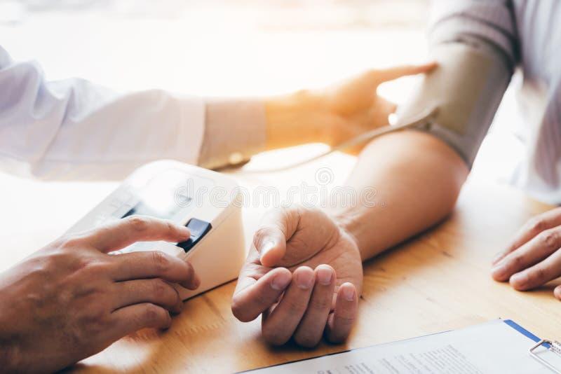Medico che per mezzo dello stetoscopio prende un rubinetto sul braccio paziente e sulla pressatura del ` s del bottone del manome fotografia stock