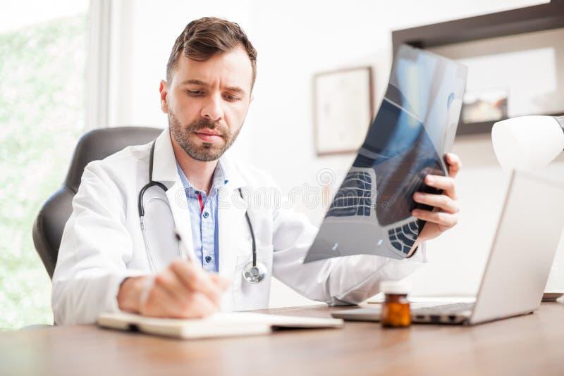 Medico che prende le note da alcuni raggi x immagine stock