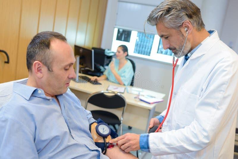 Medico che prende pressione sanguigna del ` s dell'uomo fotografie stock libere da diritti