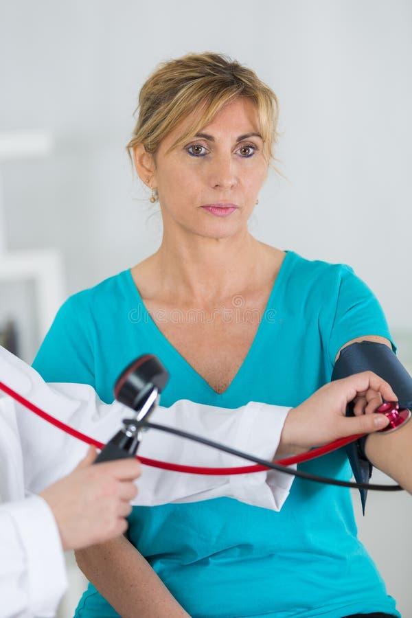 Medico che prende pressione sanguigna maturare donna immagini stock libere da diritti