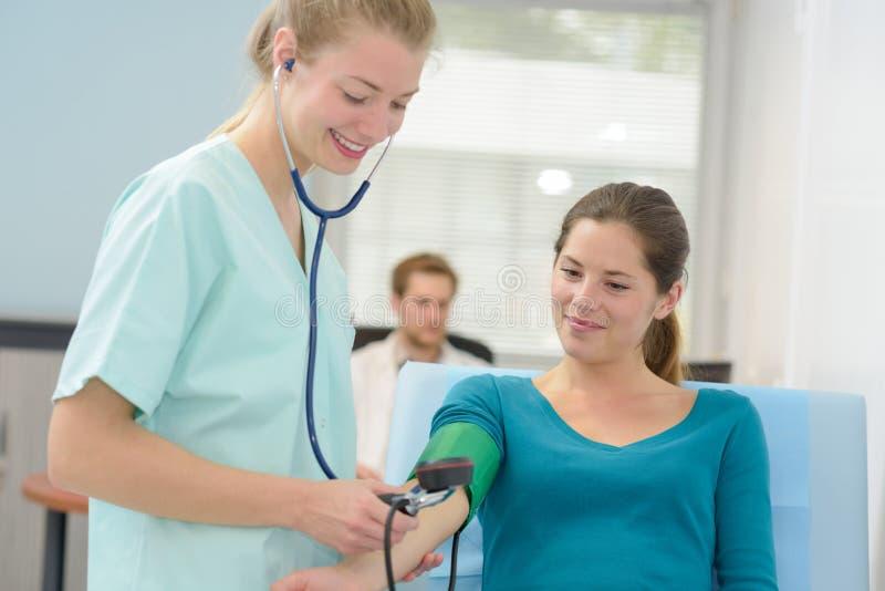 Medico che prende a pressione sanguigna paziente femminile all'ufficio fotografia stock