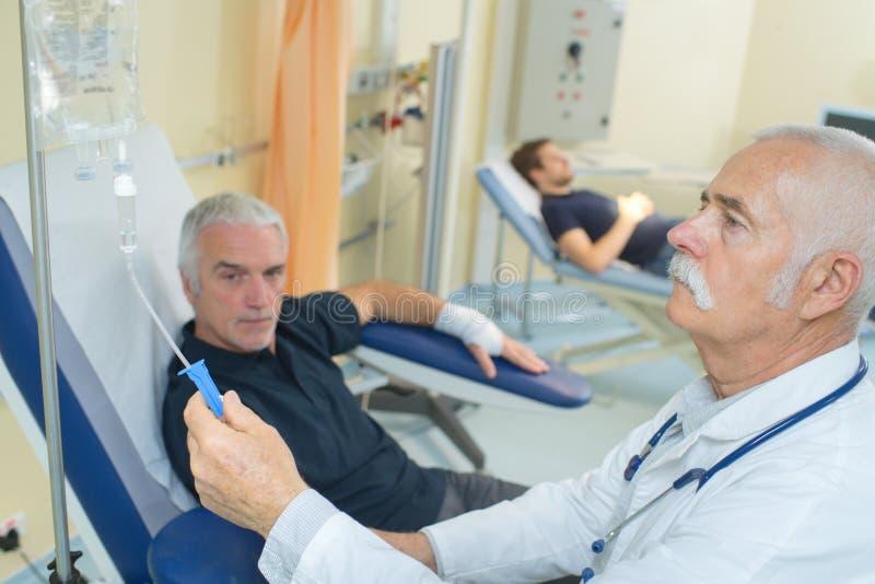 Medico che regola il gocciolamento paziente del ` s immagine stock