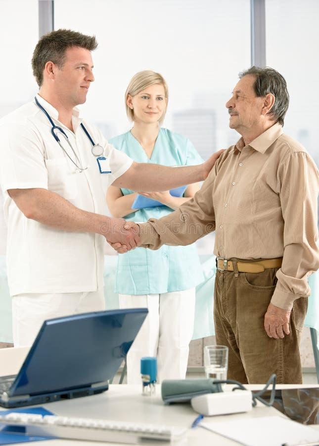 Medico Che Si Congratula Paziente Maggiore Sul Ripristino Immagine Stock