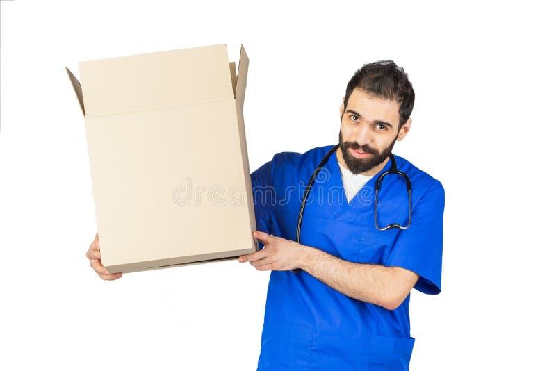 medico che sorride e che tiene una scatola sul fondo bianco dello studio fotografia stock libera da diritti