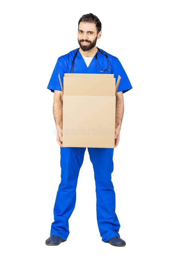 medico che sorride e che tiene una scatola sul fondo bianco dello studio immagine stock
