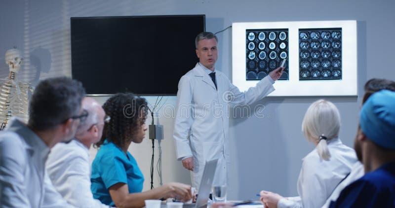 Medico che spiega diagnosi ai suoi colleghi fotografia stock libera da diritti