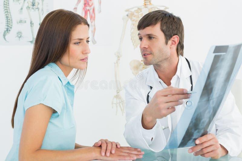 Medico che spiega i raggi x della spina dorsale al paziente femminile fotografie stock