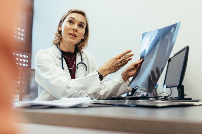 Medico che spiega risultato di controllo al suo paziente immagine stock