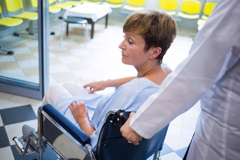 Medico che spinge paziente senior sulla sedia a rotelle fotografia stock