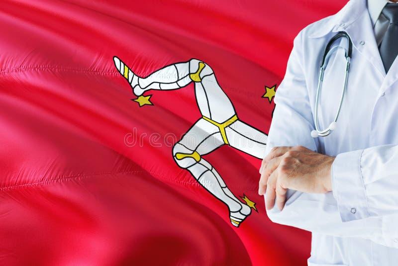 Medico che sta con lo stetoscopio sul fondo della bandiera dell'Isola di Man Concetto di sistema sanitario nazionale, tema medico fotografie stock