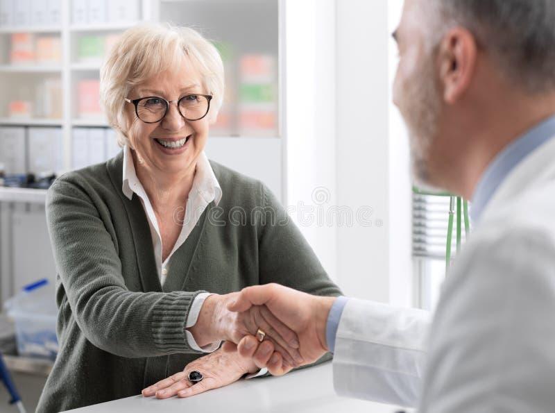 Medico che stringe le mani con un paziente senior fotografia stock libera da diritti