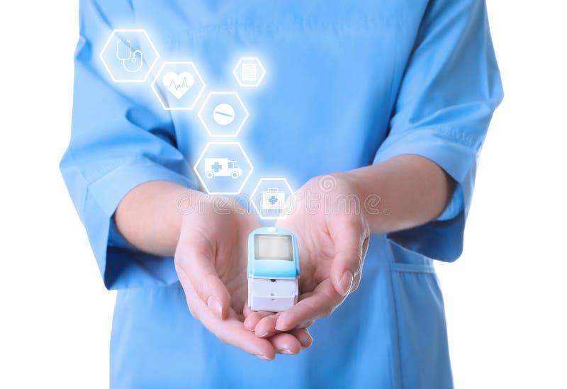 Medico che tiene apparecchio medico moderno e le icone informative su fondo bianco fotografia stock libera da diritti