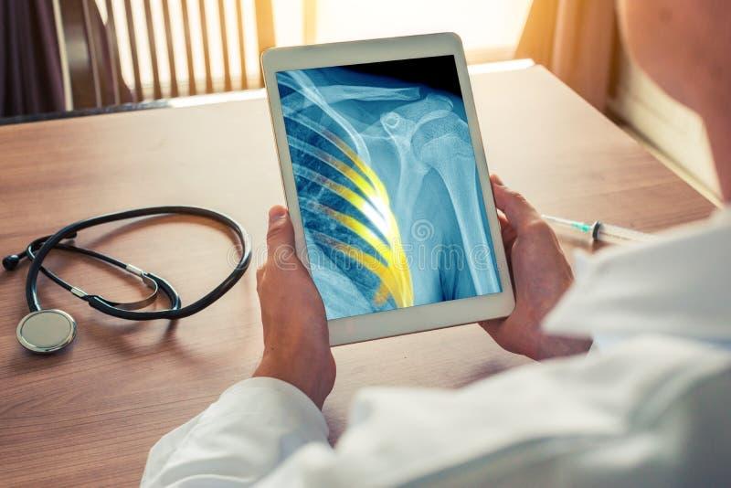 Medico che tiene una compressa digitale con i raggi x del petto con dolore sulle costole Stetoscopio e siringa sullo scrittorio immagine stock