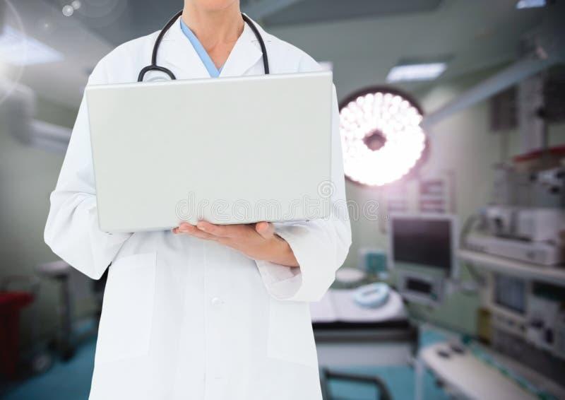 Medico che utilizza computer portatile contro la sala operatoria nel fondo immagine stock libera da diritti
