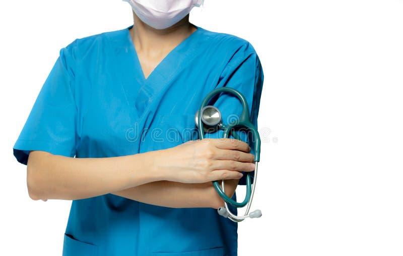 Medico chirurgo o infermiere indossa un'uniforme da camice blu e una maschera rosa Supporto medico con braccia incrociate e tenut immagine stock