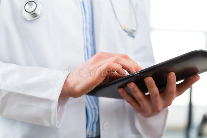 Medico in clinica che legge archivio digitale sul computer della compressa fotografia stock