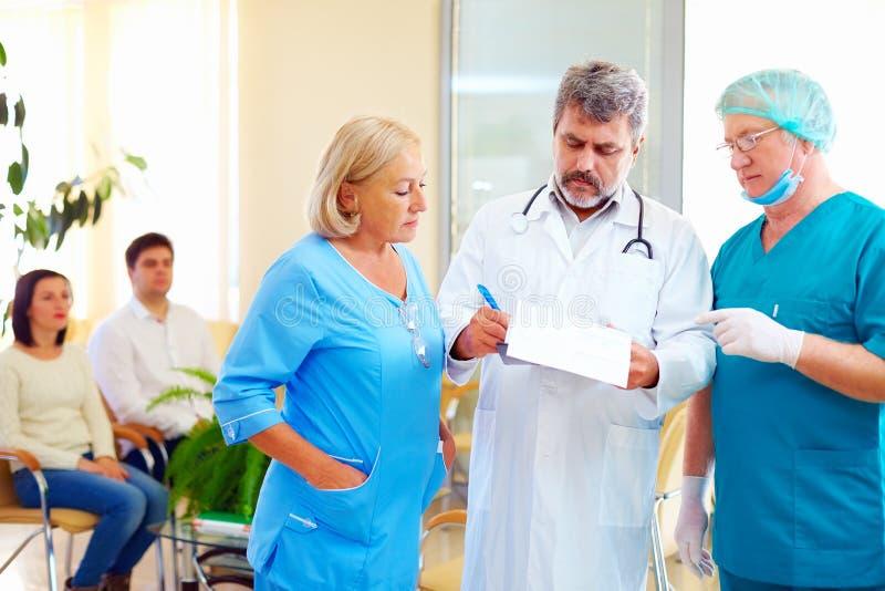 Medico con esperienza e personale medico che si consultano circa la cartella medica in ospedale immagini stock