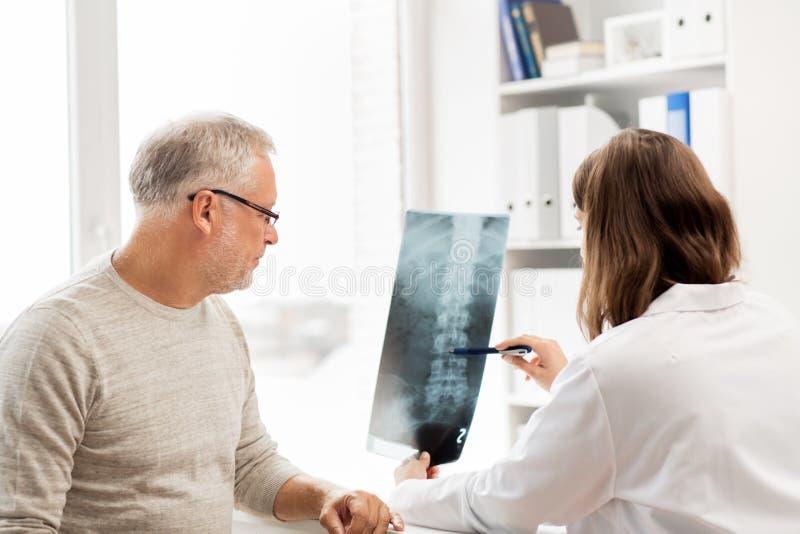 Medico con i raggi x della spina dorsale ed uomo senior all'ospedale immagini stock