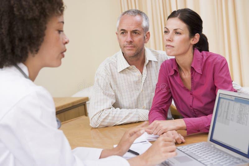 Medico con il computer portatile e le coppie nell'ufficio del medico immagine stock