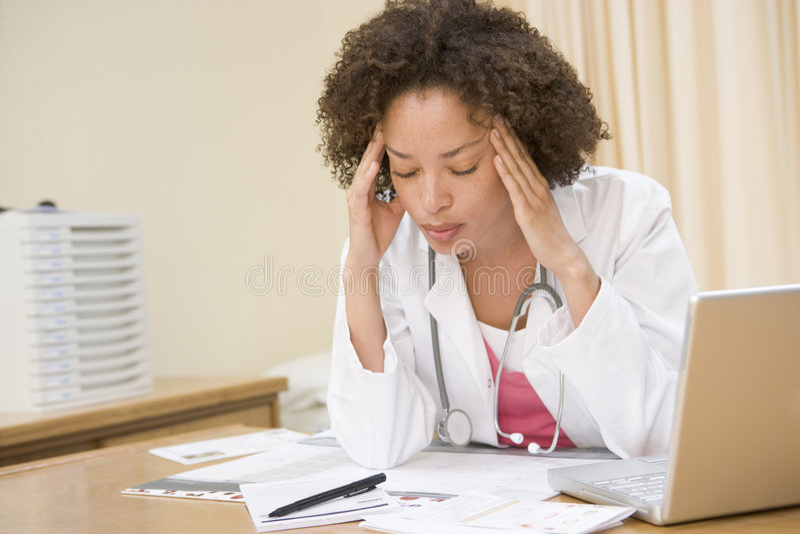 Medico con il computer portatile ed emicrania nell'ufficio del medico fotografia stock libera da diritti
