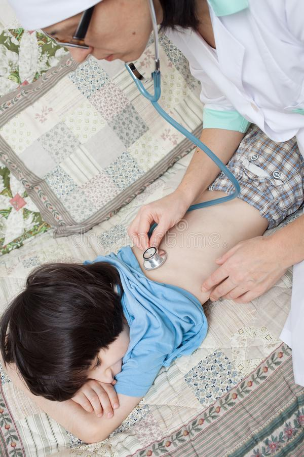 Medico con il respiro del bambino d'ascolto dello stetoscopio fotografia stock