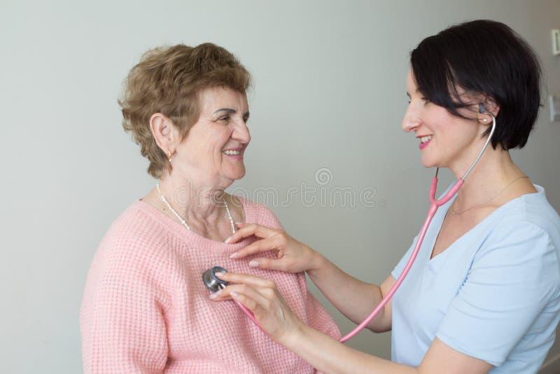 Medico con l'esame medico sorridente dello stetoscopio paziente anziano della donna immagine stock libera da diritti