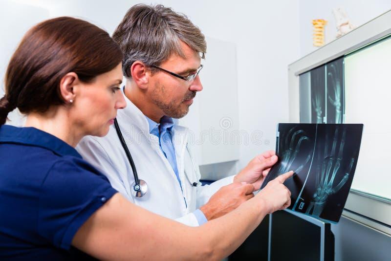 Medico con l'immagine dei raggi x della mano paziente fotografie stock