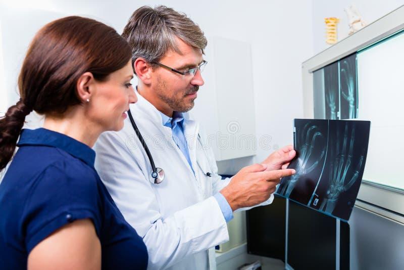 Medico con l'immagine dei raggi x della mano paziente fotografia stock libera da diritti