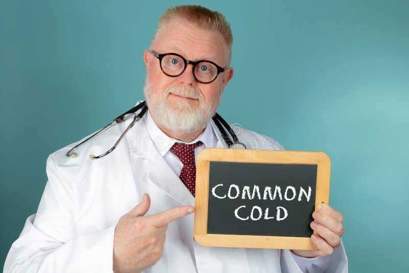 Medico con l'iscrizione di raffreddore della lavagna immagini stock