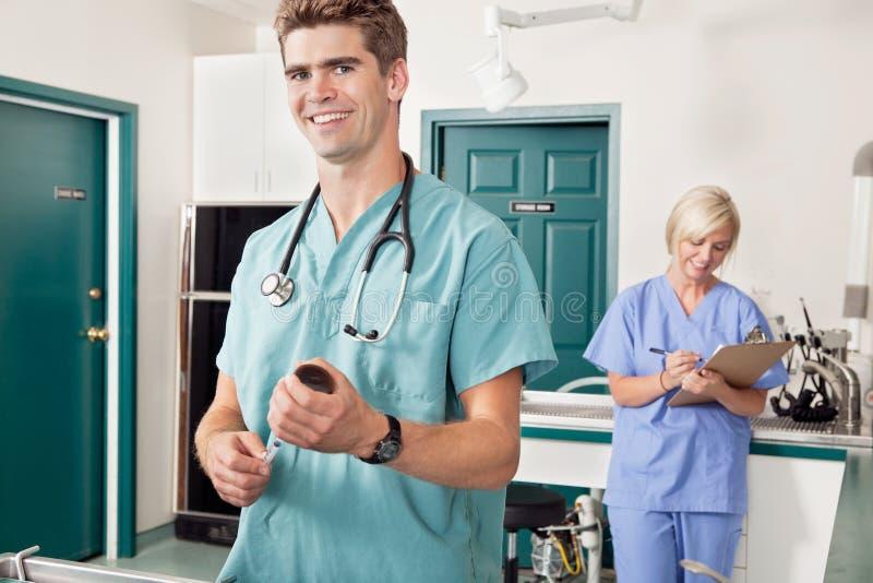 Medico con la siringa mentre infermiera che cattura giù il rapporto fotografie stock libere da diritti