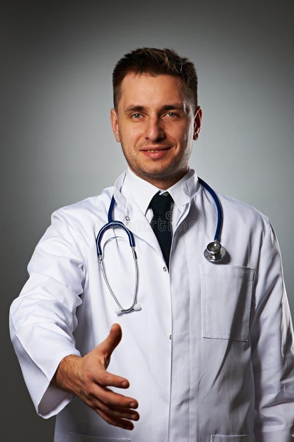 Medico con lo stetoscopio che dà mano per handshake immagini stock libere da diritti